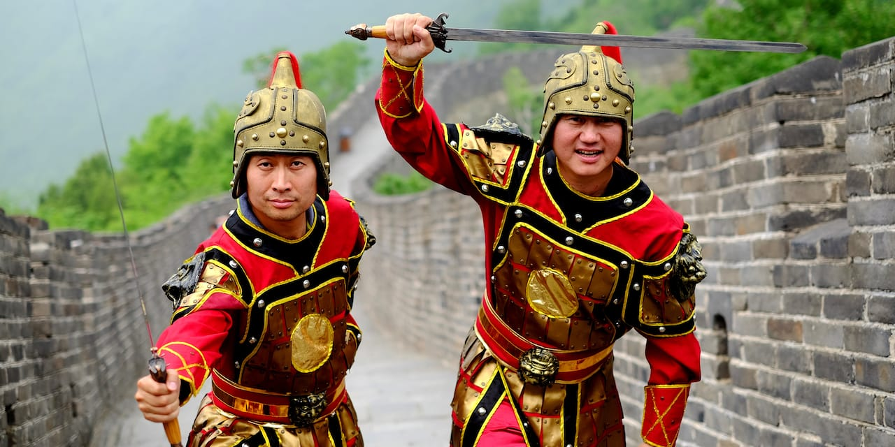Two costumed Chinese guards with swords on the Great Wall of China