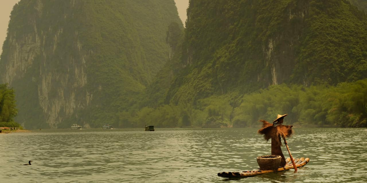 A fisherman on a bamboo raft cruises down the Li River