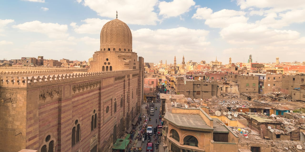 A large building with a domed structure at its far end amid the city of Cairo, Egypt under a cloudy sky