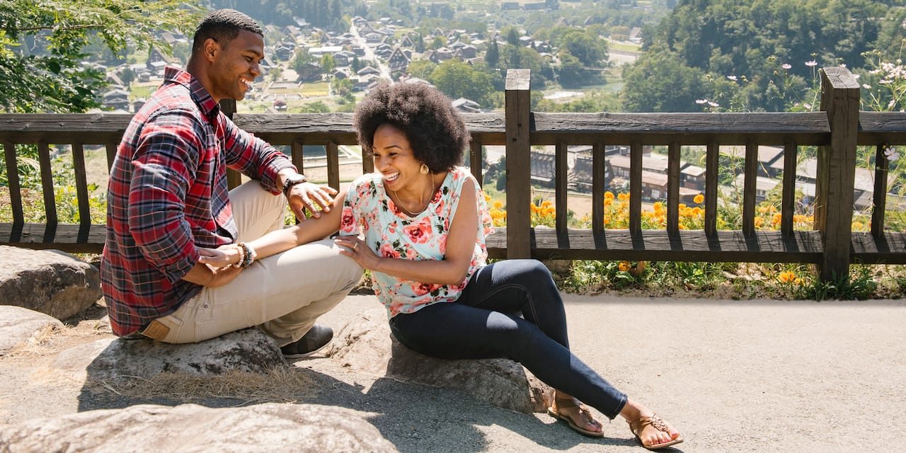 A man and a woman sit on a rock near a wooden fence overlooking a village in a lush mountain valley