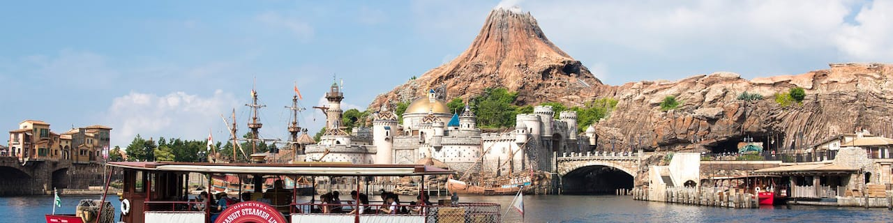 A steamship passes in front of the domed fortress at the base of Mount Prometheus volcano in Tokyo DisneySea