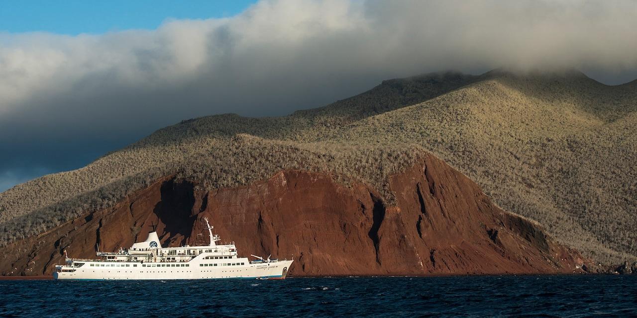 A cruise ship coasts along Rabida Island