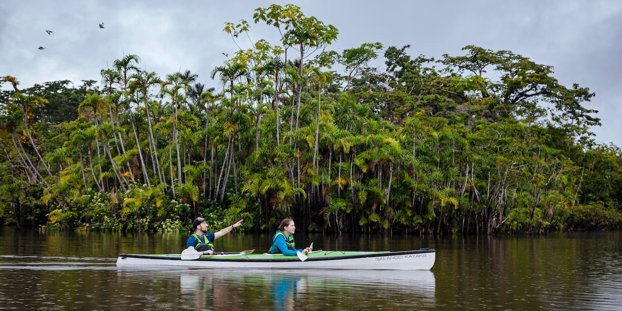 A man, pointing to something in the distance, and a woman ride in a canoe on a river near a tree lined bank