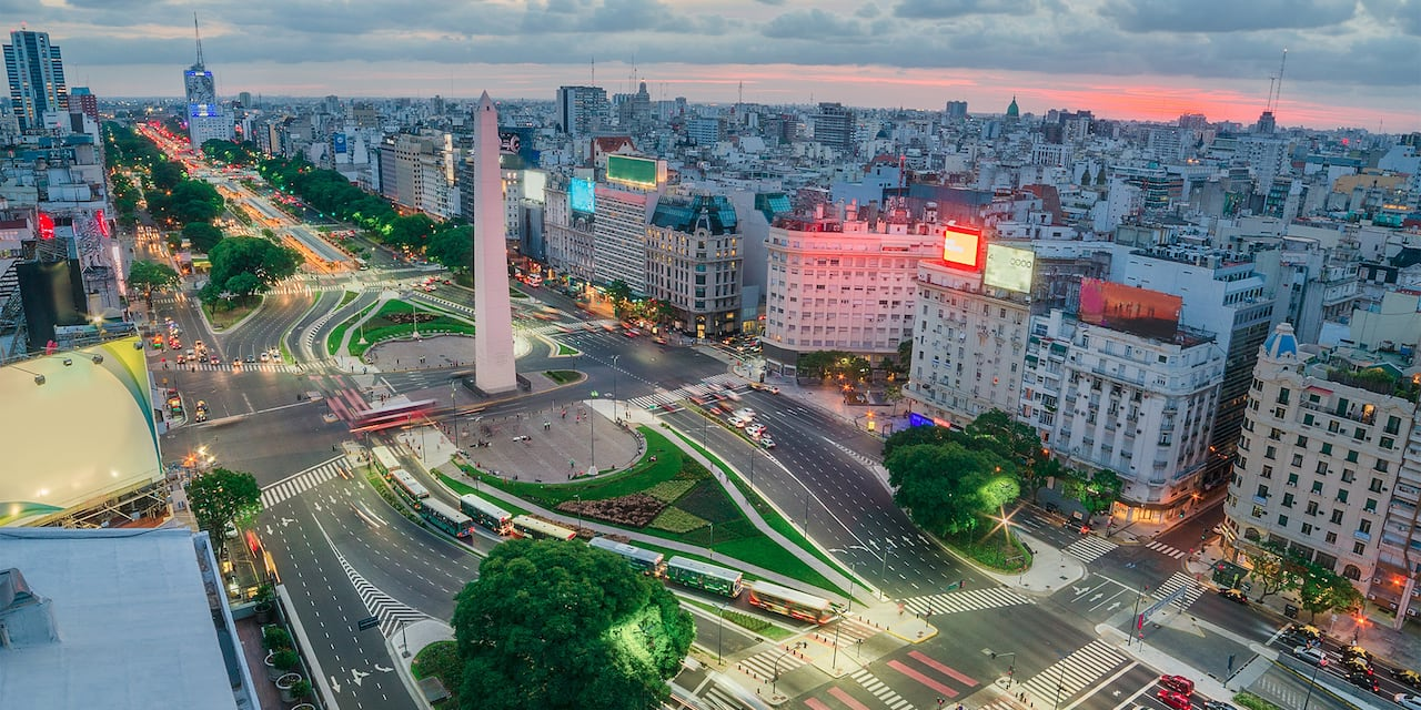 An aerial image of he city of Buenos Aires at dusk with the Obelisco in the middle of a large intersection