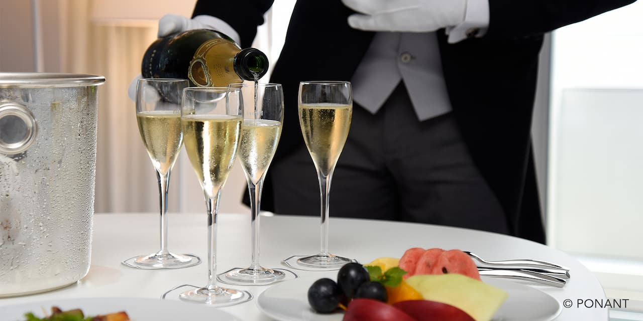 A white gloved server pouring chilled champage into four flutes with a fruit plate on the table