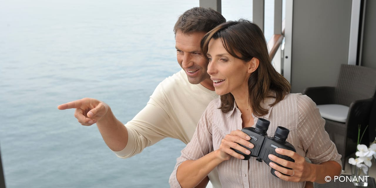 A couple looking out from their cruise ship balcony