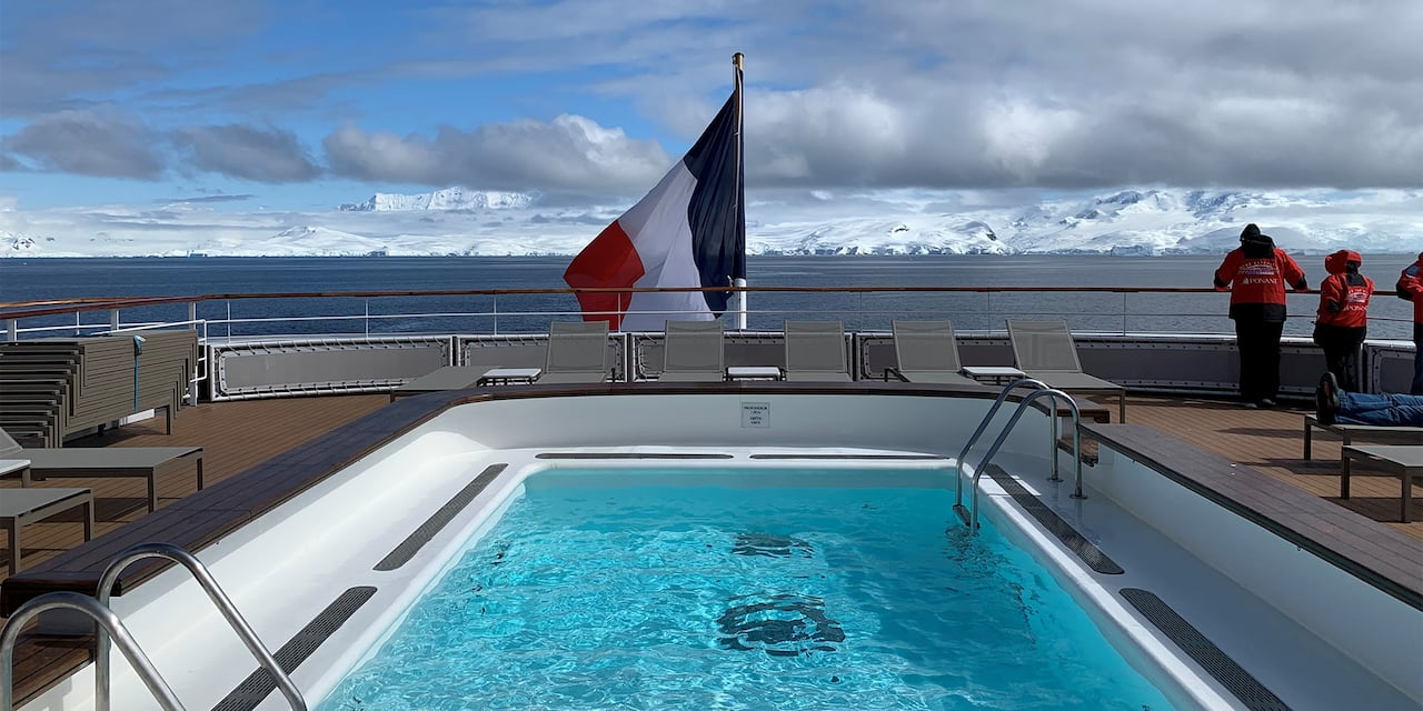 Top deck pool looking out to the French flag posted at the stern of the boat and the snowcapped mountains of Antarctica in the distance