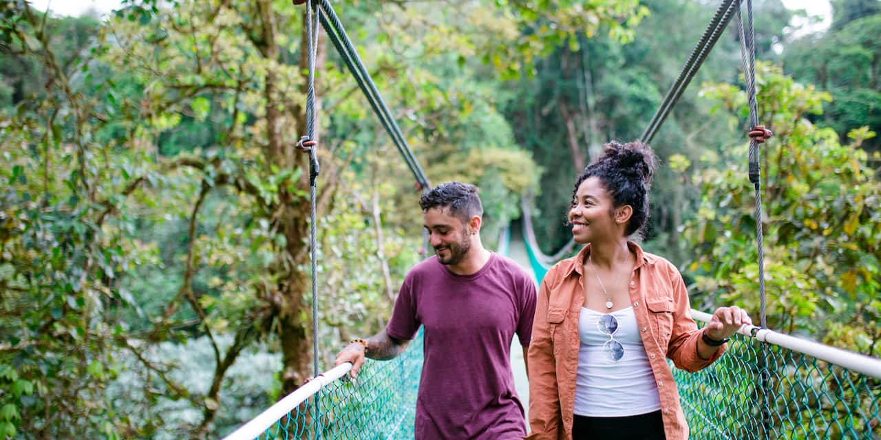 A smiling couple crosses a hanging bridge in a lush nature preserve