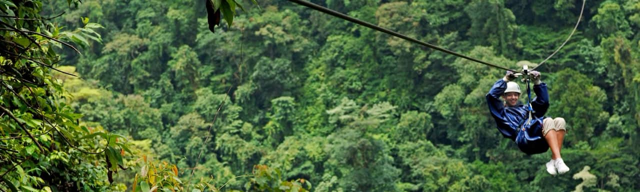 A tourist zip lines through the rainforest