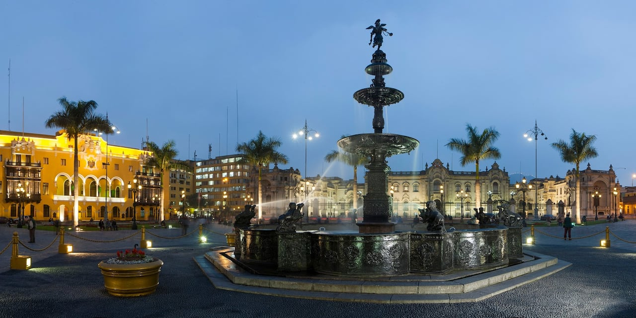 A fountain with a trumpeter at the top on the cobblestone streets of Plaza Mayor in Lima, Peru