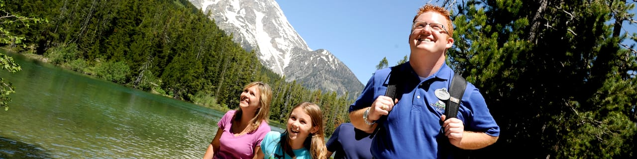 A mom, daughter and Adventure Guide hike through the wilderness