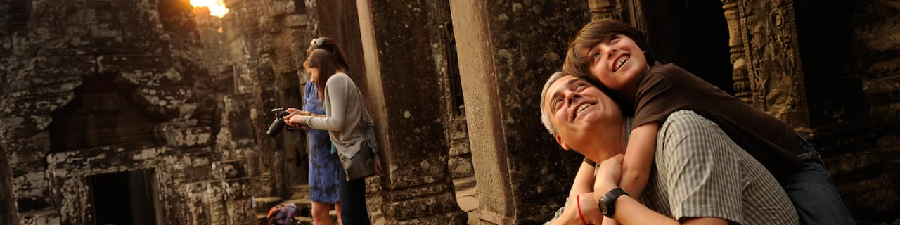 A dad and son view ancient ruins with other tourists nearby