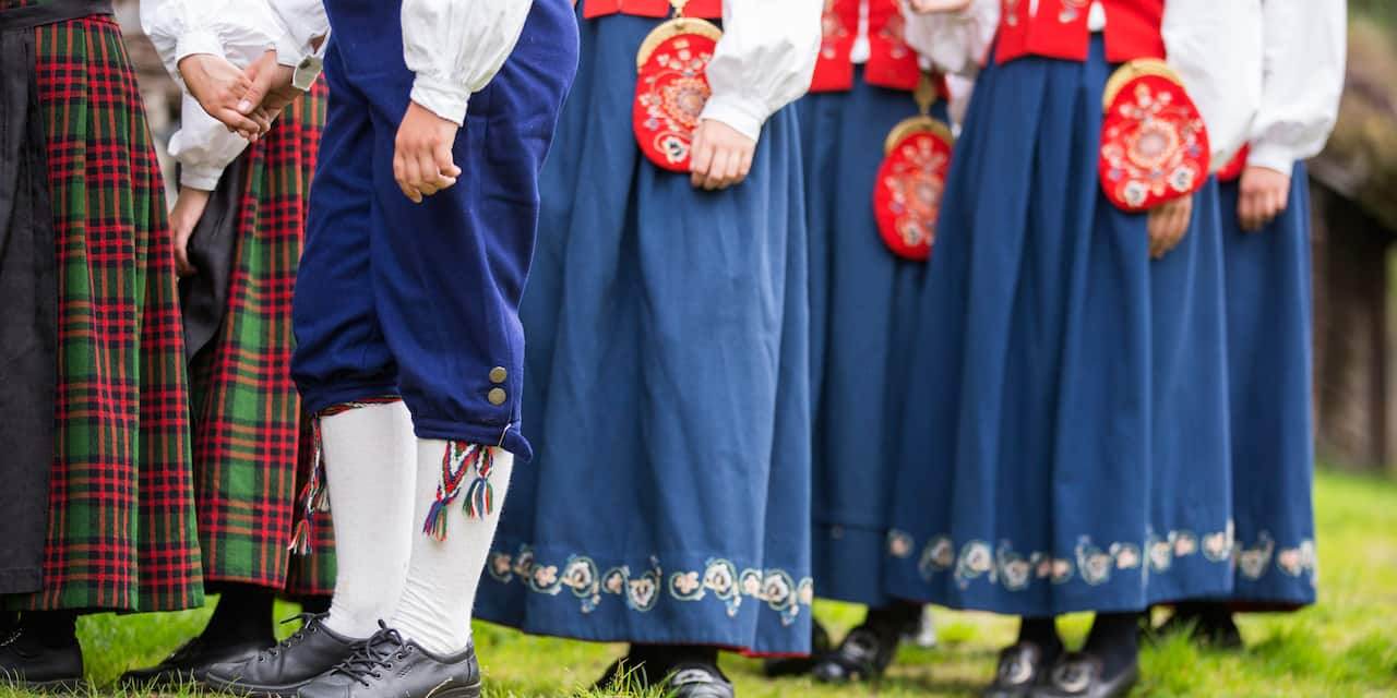 A group of Norwegian men and women, dressed in traditional costumes, are seen from the waist down
