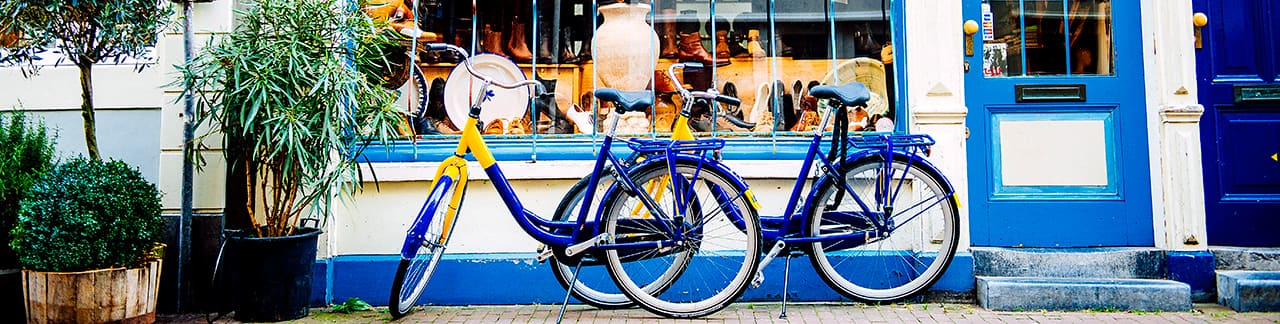 Two bicycles parked in front of a local shop