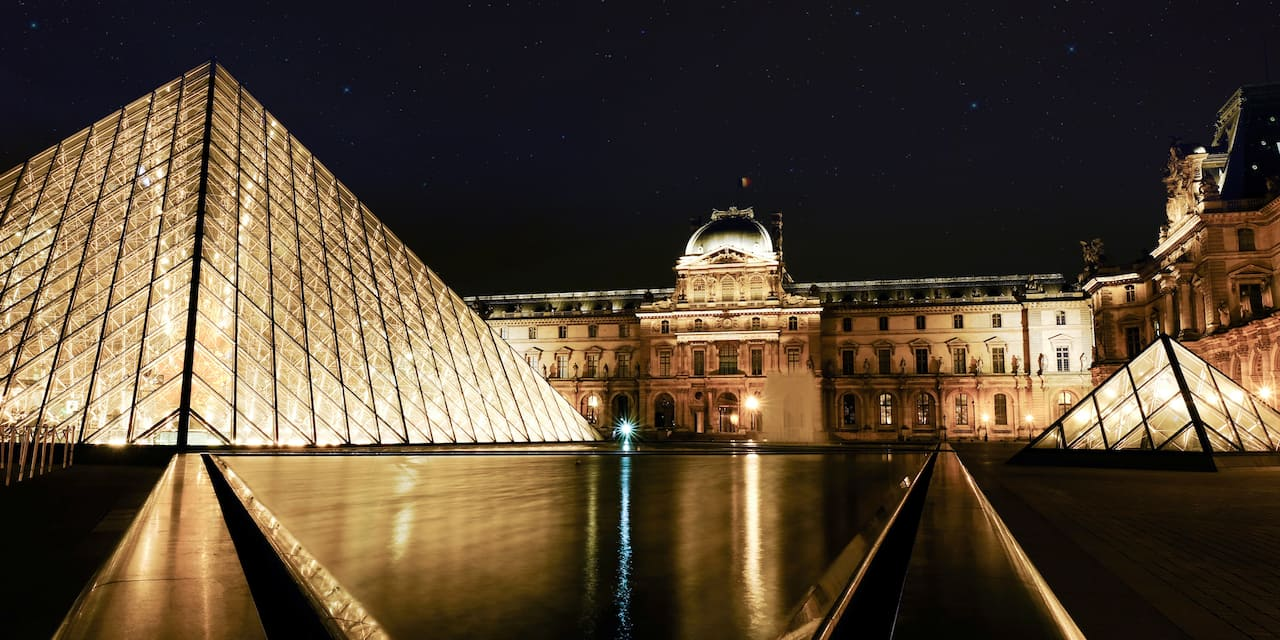 The glass pyramids and the main building of the Louvre Museum in Paris, France lit up at night
