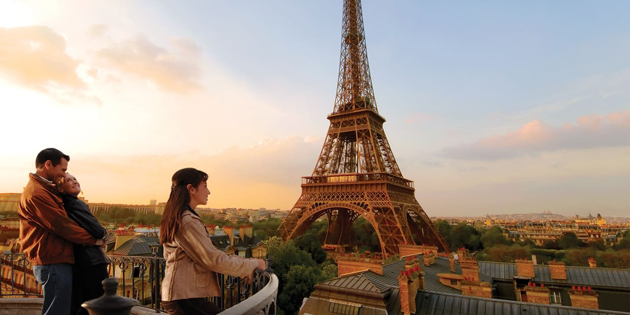 A family of 3 look out at the Eiffel Tower
