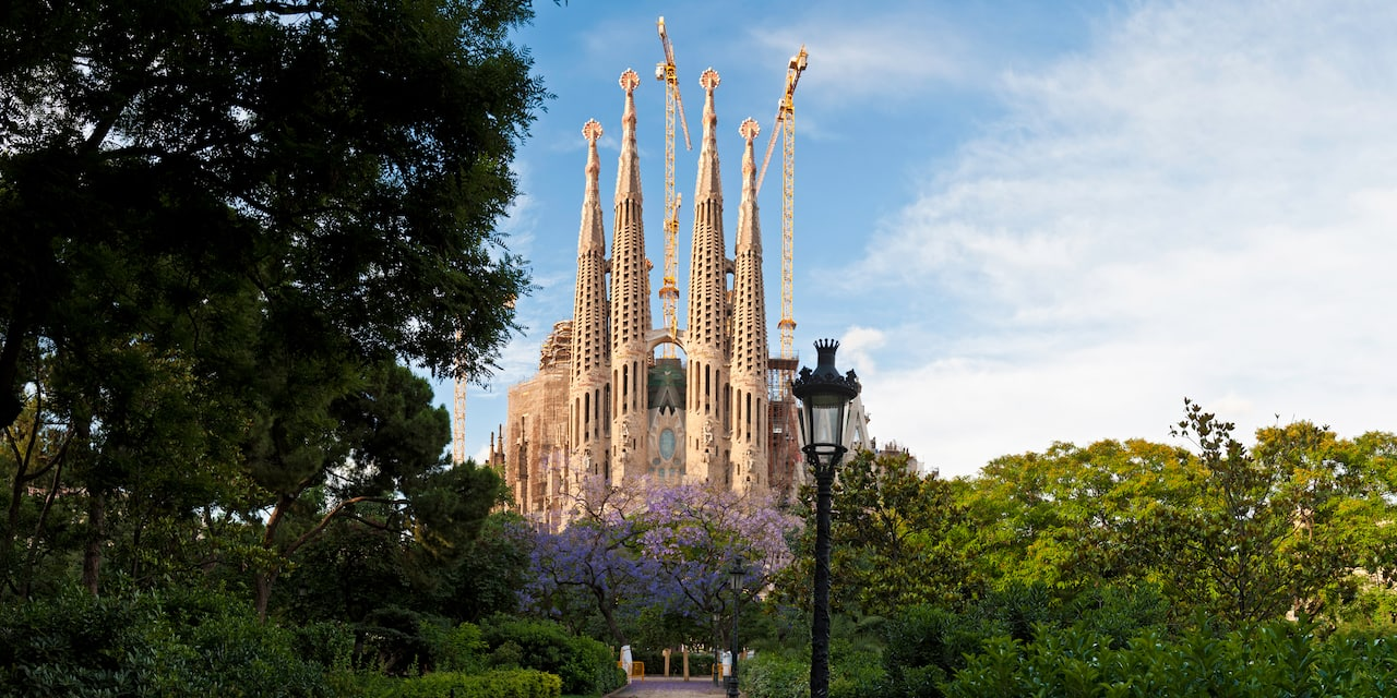 The spires of La Sagrada Familia and some construction cranes stand amid the trees and a lamppost of the surrounding park in Barcelona, Spain