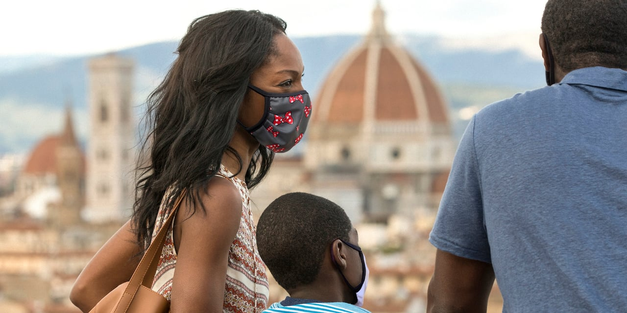 Family wearing masks stand on terrace overlooking the city of Florence