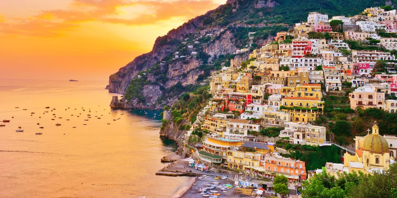 Colorful Positano houses stacked against the mountain with the reflection of the sunset on the sea