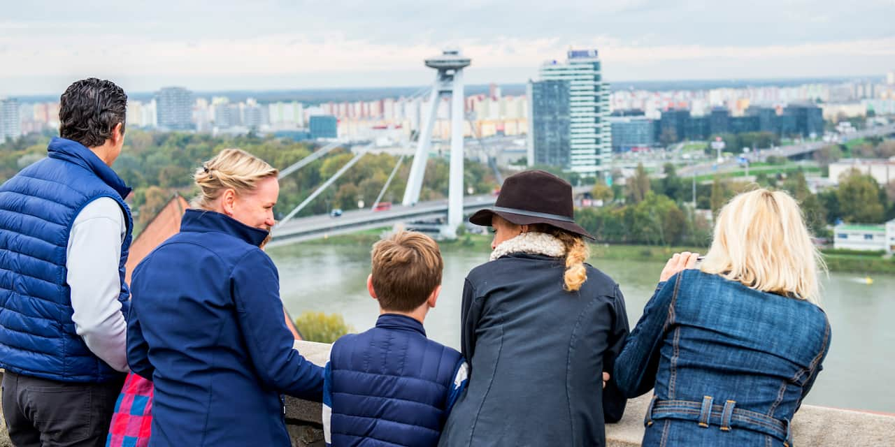 A family stands near a bridge and looks across a river at a modern city