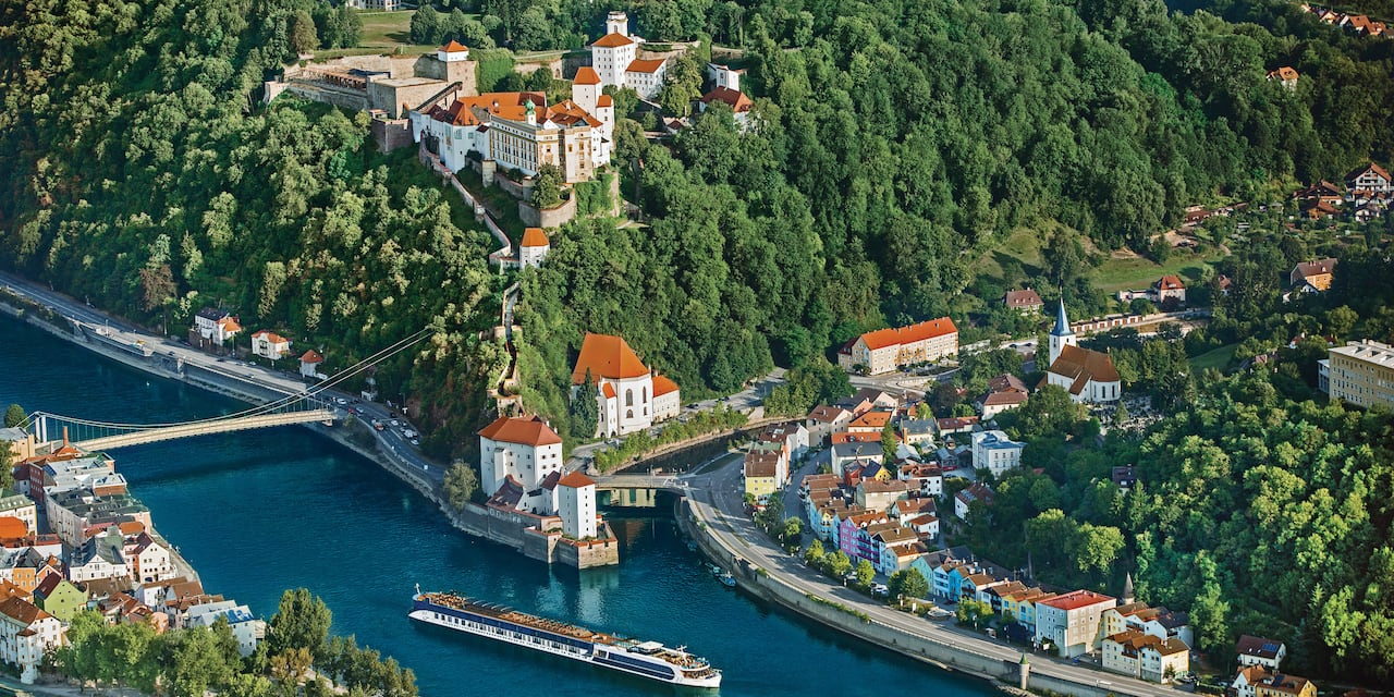 A river cruise ship sails on the Danube River through Passau, Germany and its lush landscape
