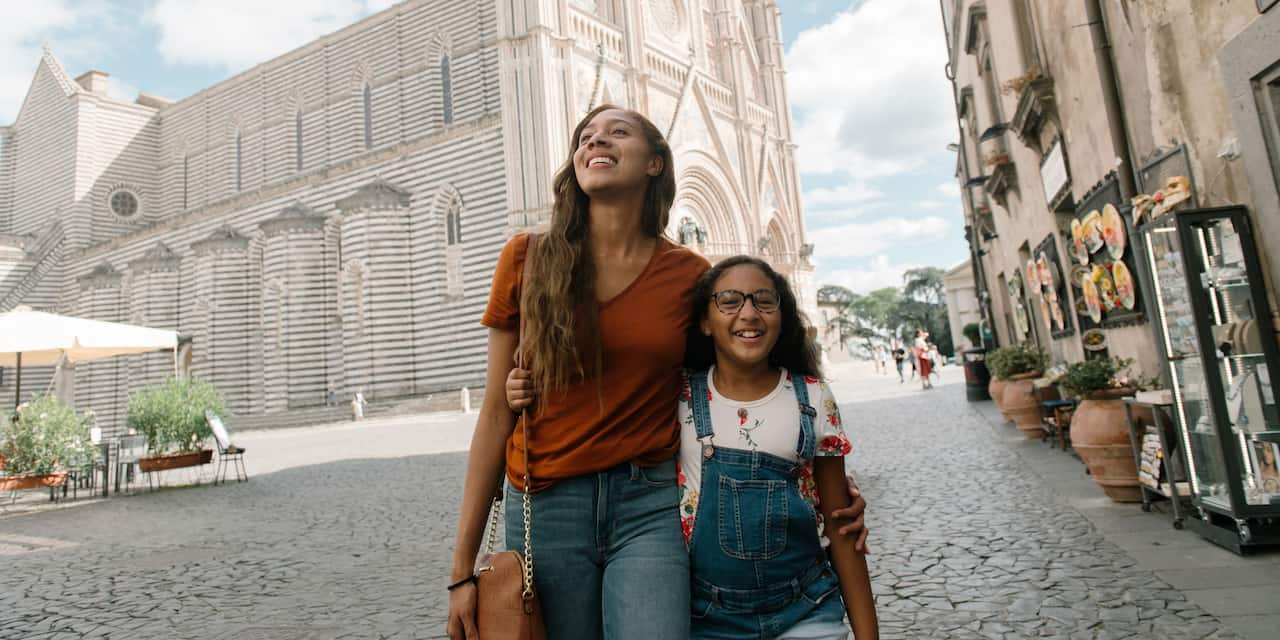 A mother and a daughter walk down a street arm in arm in Italy