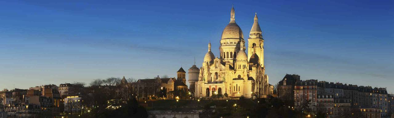 The Basilica of the Sacré Cœur is lit up high on Montmartre at dusk