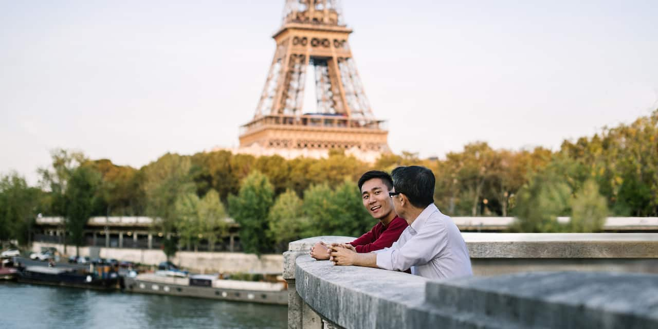 Two men talking with their arms resting on a stone wall that overlooks a river with the Eiffel Tower in the background