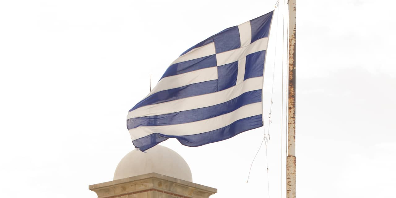 The Greek flag atop a flagpole billows in the wind