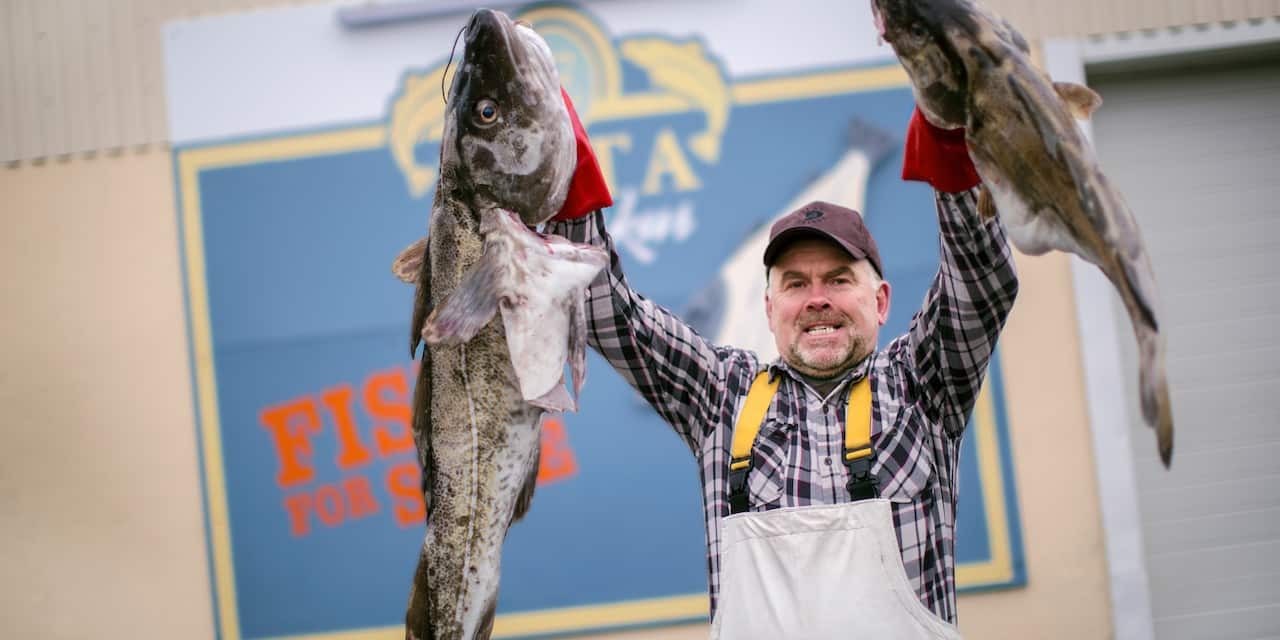 "A smiling man wearing a cap and apron holds 2 large fish in front of a sign that reads, ""EKTA Fiskus: Fish for Sale"""