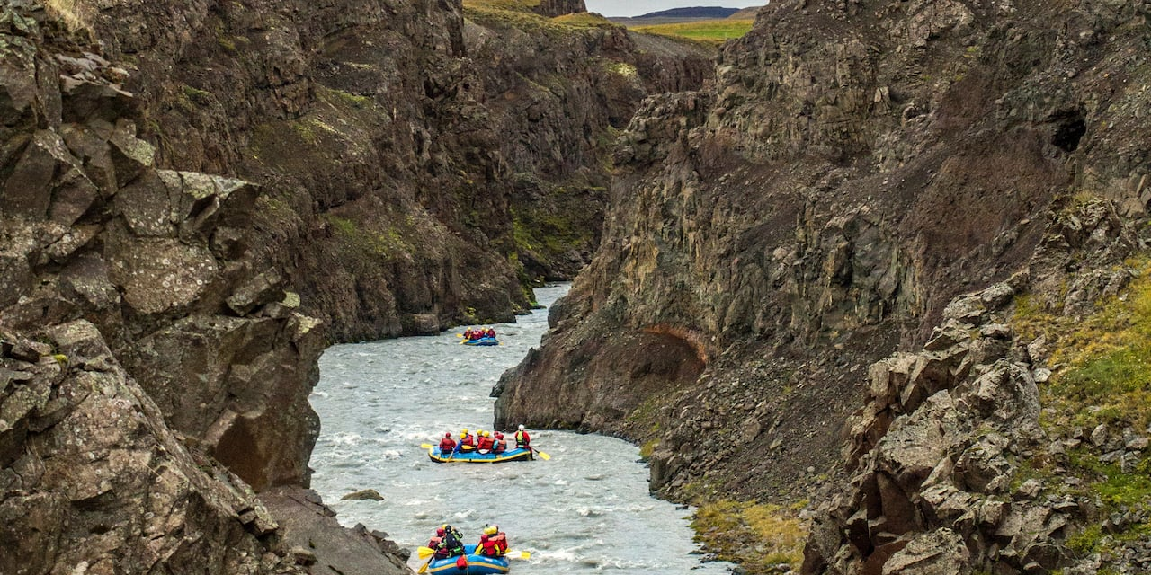 A group of 3 rafts are white water rafting between the rocky terrain of Skagafjörður