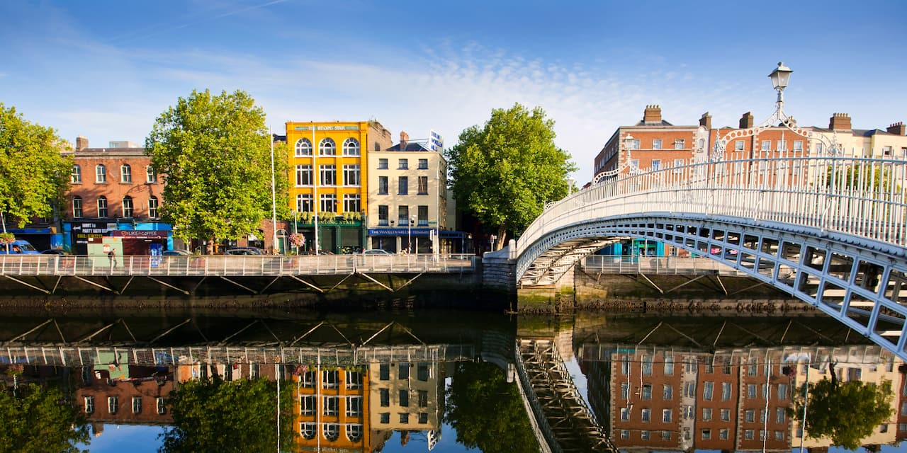 Dublin's cast iron Ha'penny Bridge spans the River Liffey to a building-lined street, which is reflected in the river below