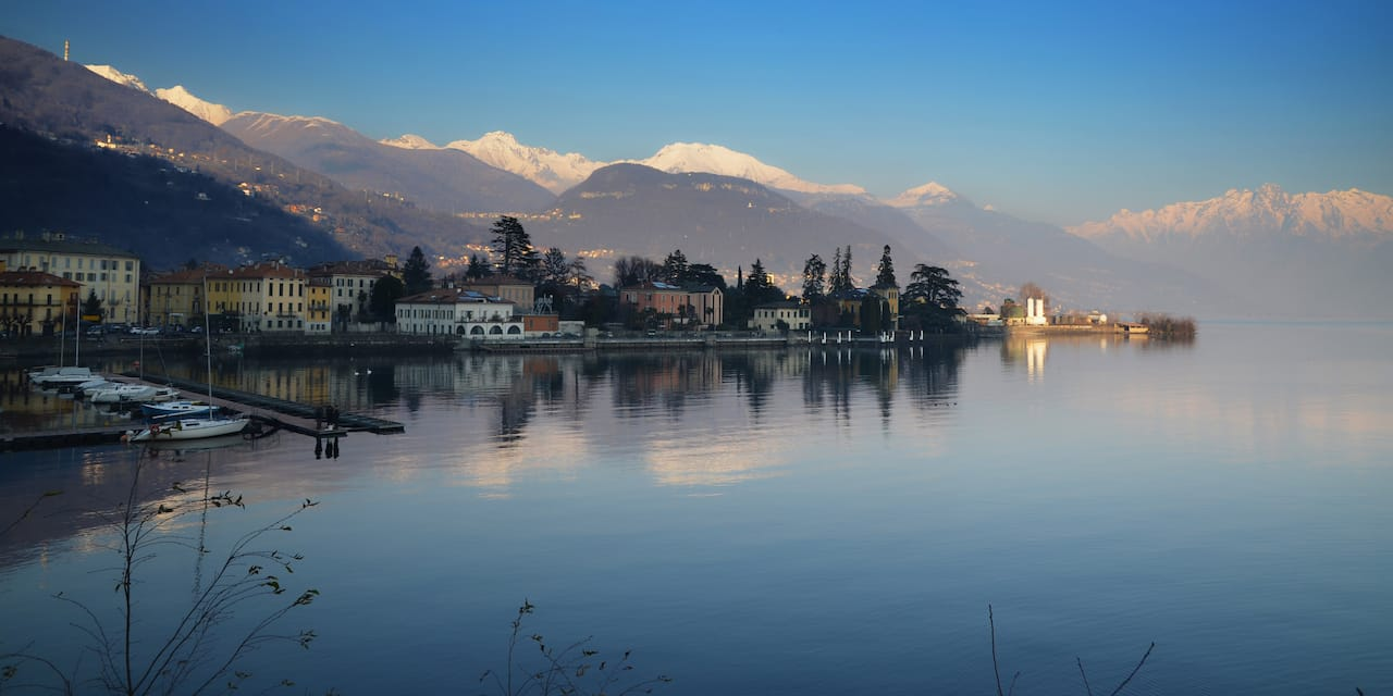 A calm lake reflecting clouds is surrounded by villas and mountains