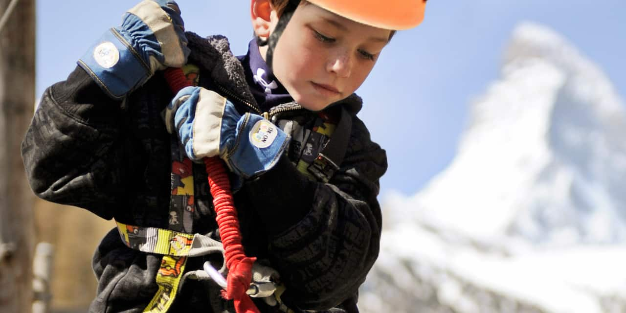 A boy wearing an athletic helmet grasps a rope with his gloved hands