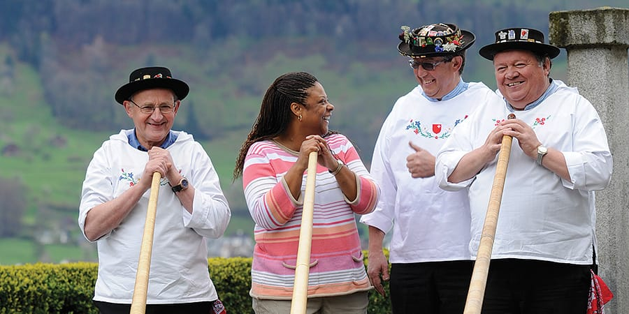 A woman stands with 3 costumed Swiss alpine horn players and laughs as she takes one of their horns