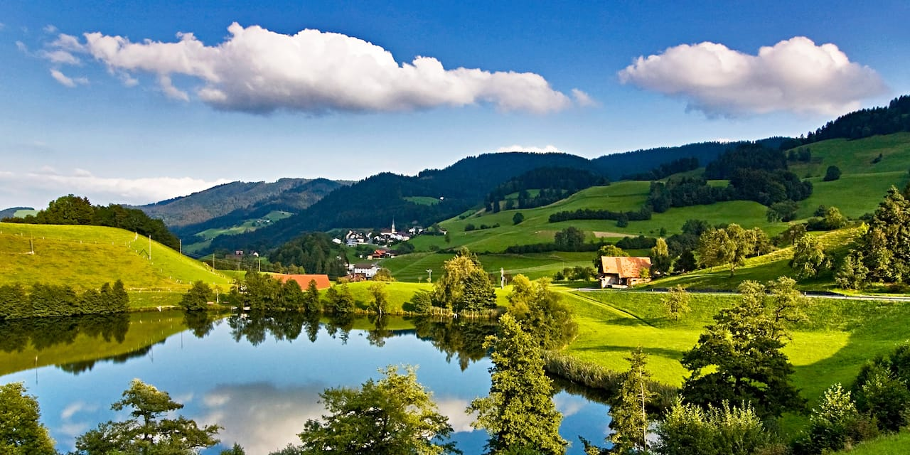 A farm near a lake and a village in a picturesque countryside with grass and rolling hills