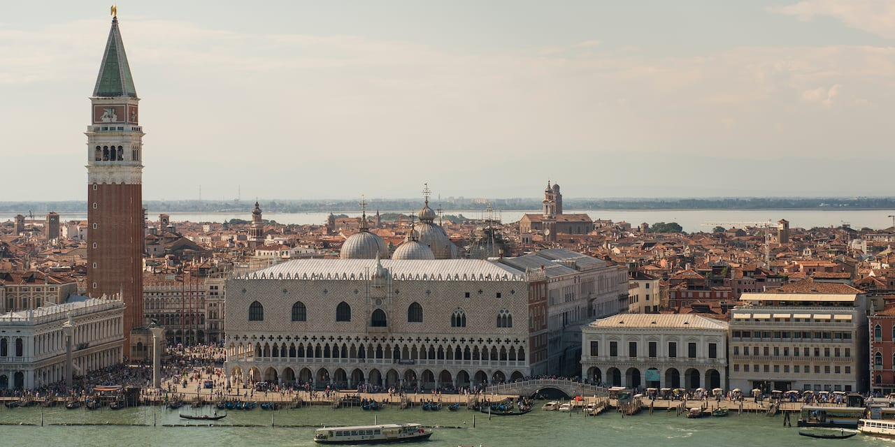 The city of Venice, Italy, including Doge's Palace and the spired St. Mark's Campanile, along a body of water