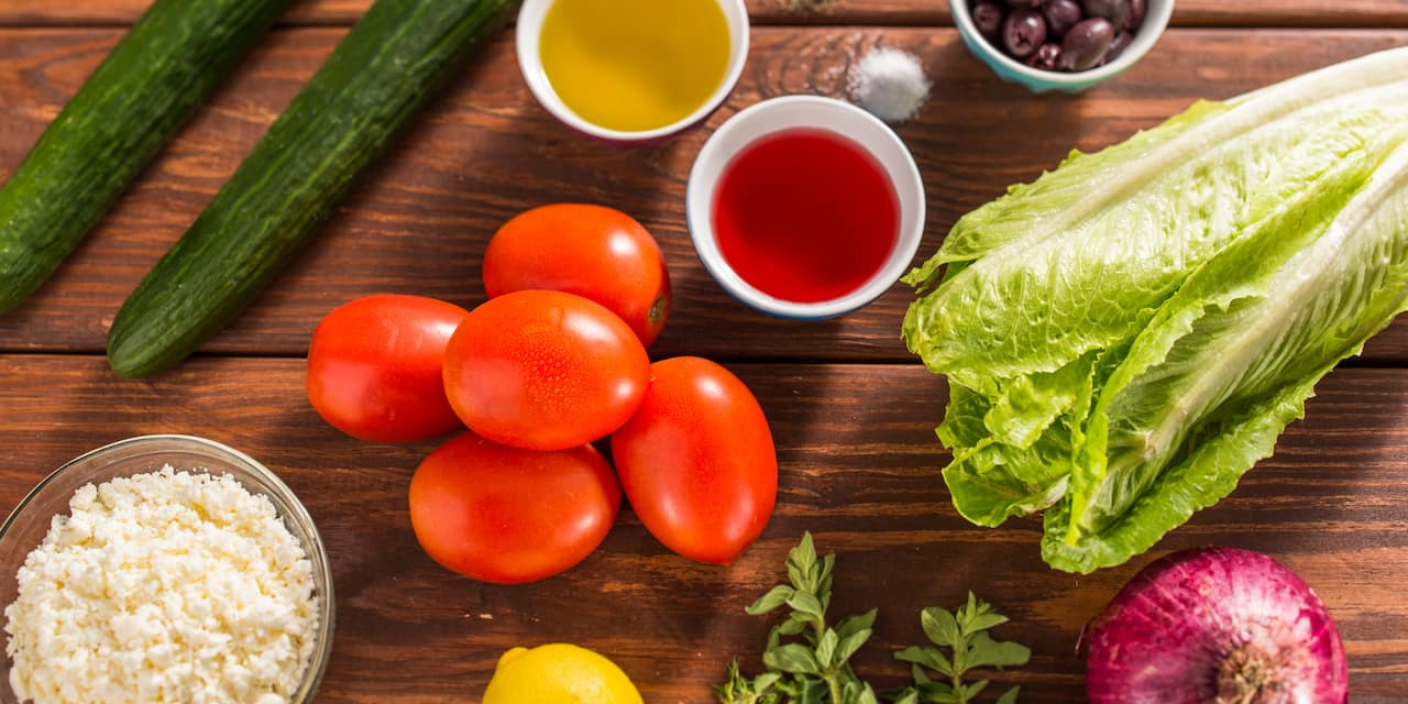 Fresh ingredients including 2 cucumbers, 5 Roma tomatoes, a head of lettuce, 1 lemon, 1 onion, a bowl of feta cheese, a bowl of greek olives, 2 bowls of dressing laid out on a wooden table