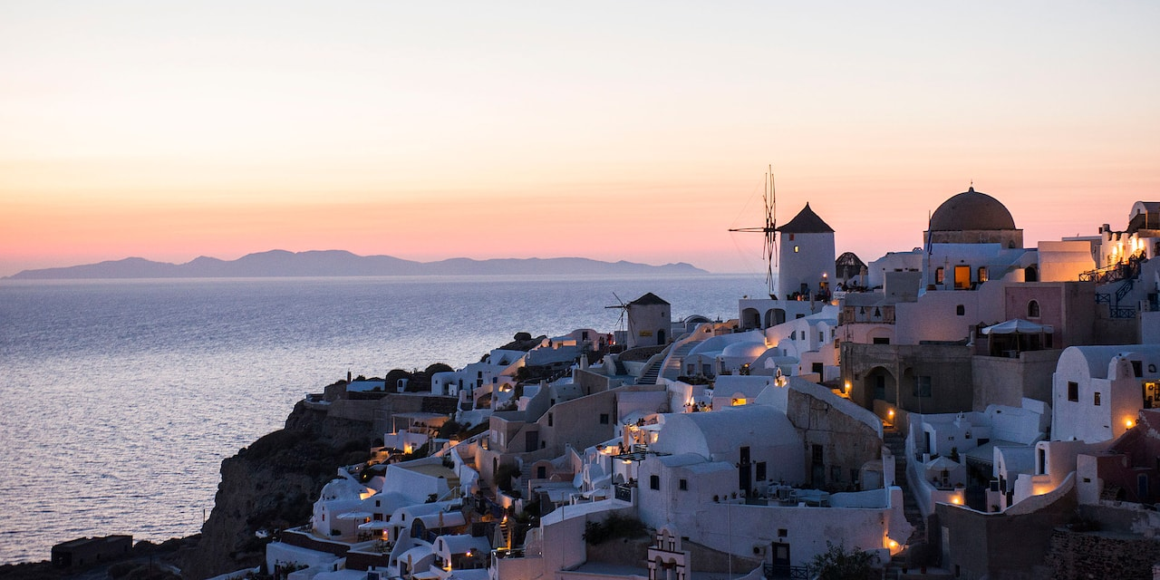 Buildings of the cliffside city of Santorini, Greece overlooking the Mediterranean Sea at nighttime