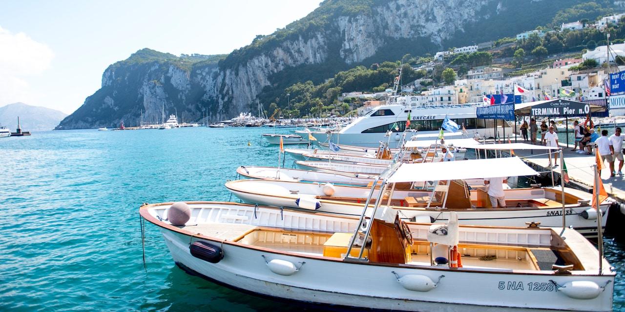 Boats anchored in a Capri Island marina near large, tree-lined cliffs