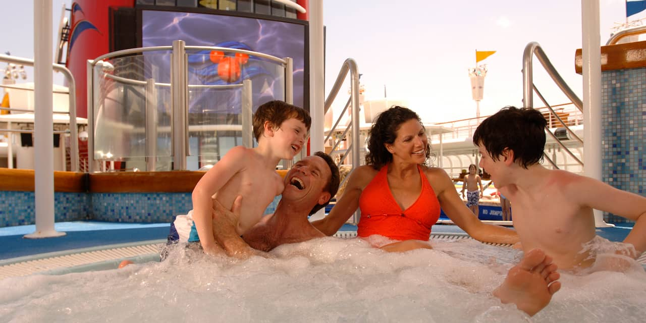 A family of 4 having in the bubbly water of a pool on the top deck of the Disney Magic cruise ship