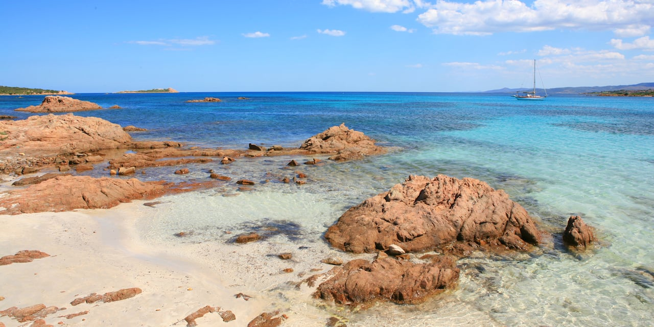 Some rocks in the water off a beach in Olbia, Italy, with a sailboat in the distance