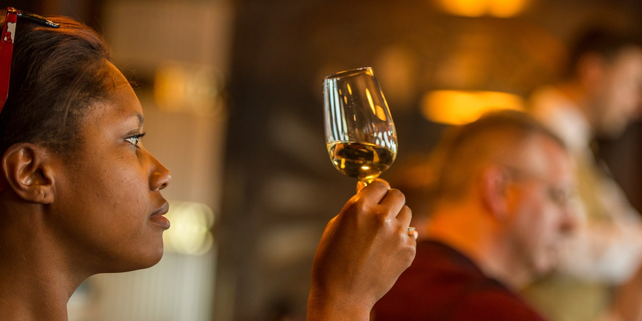 A woman inspects a glass of wine