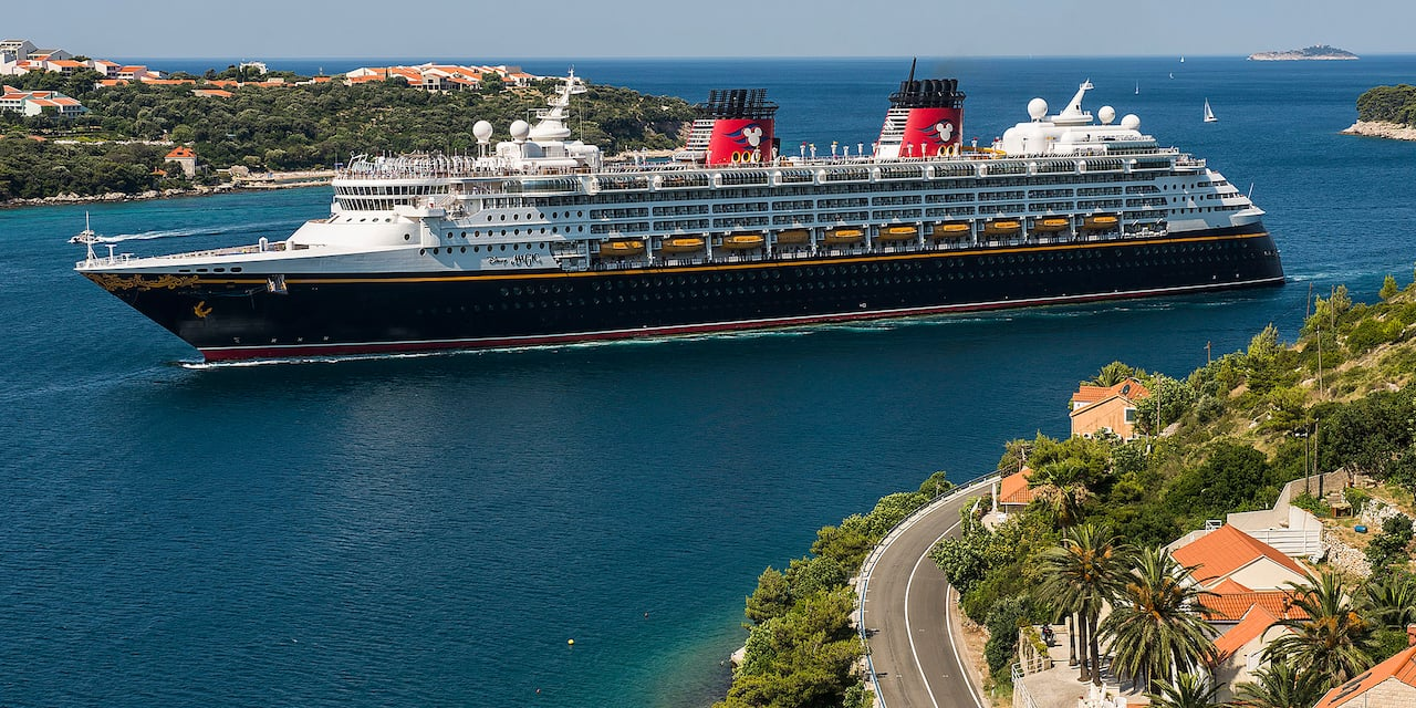 The Disney Magic Cruise Ship sails between two pieces of land with sail boats sailing in the distance