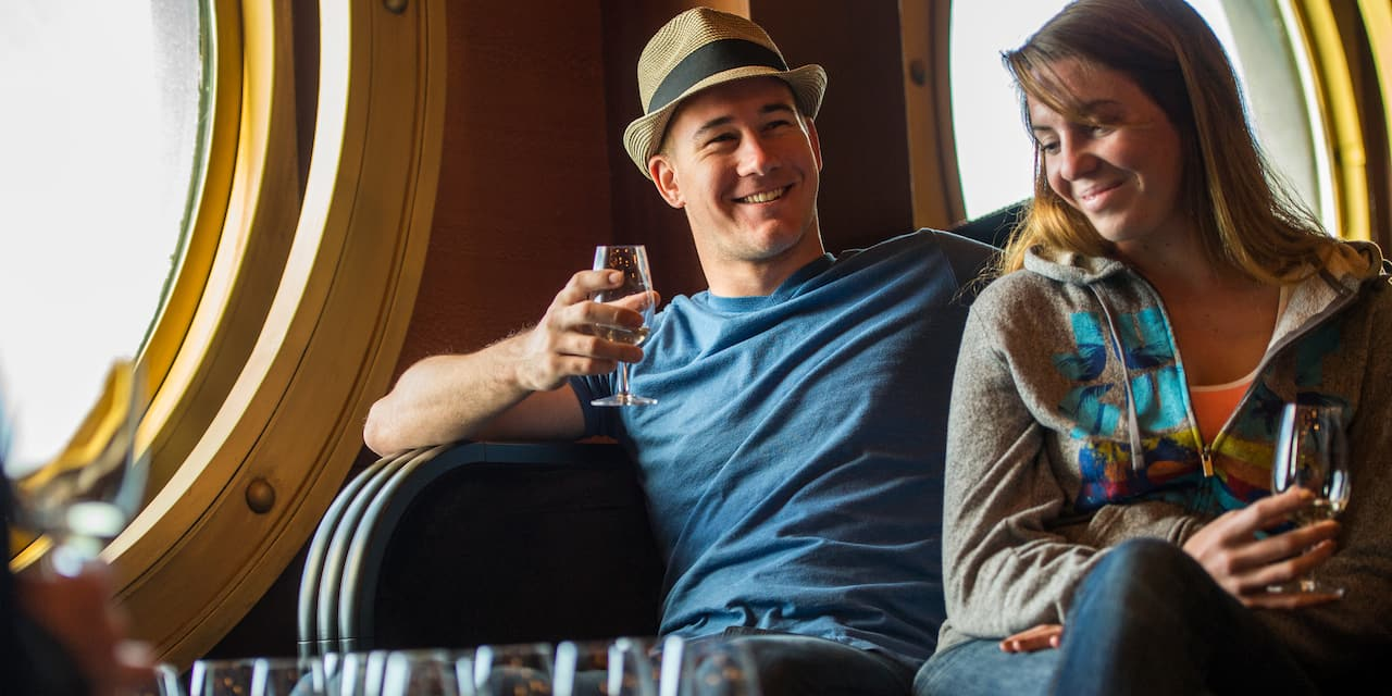 A man in a hat and woman drink cocktails onboard a ship