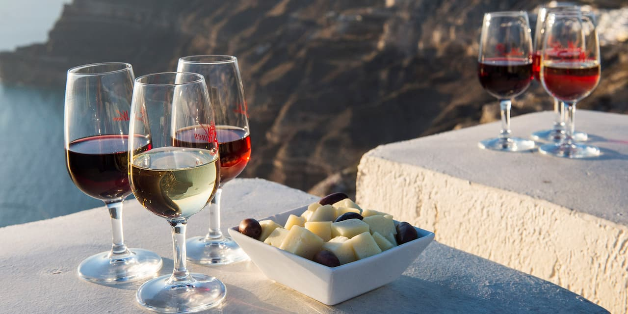 Six glasses of wine and a dish of cheese and olives sit on a ledge overlooking mountains near the sea