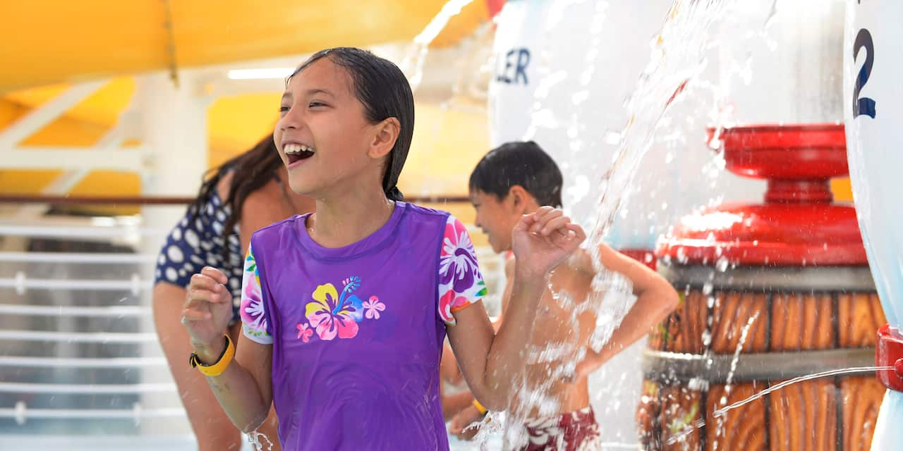 Kids get squirted with water while playing in the AquaLab water playground on the Disney Wonder cruise ship