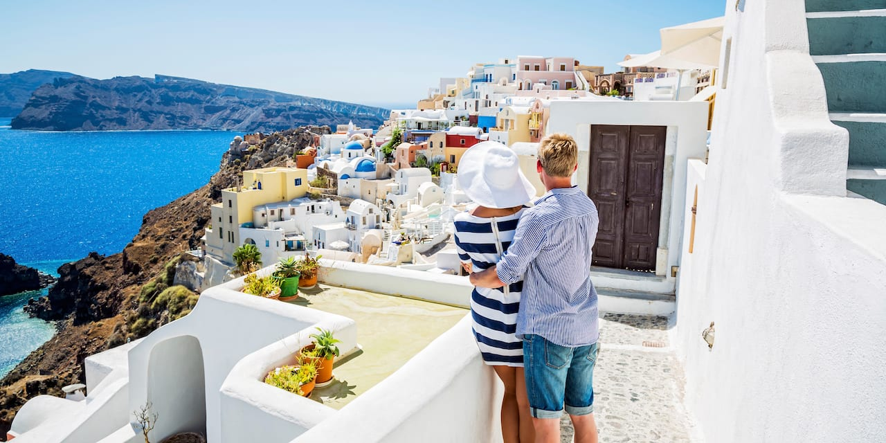 A man has his arm around a woman's waist as they look out over the city of Santorini, Greece and the Aegean Sea from a balcony