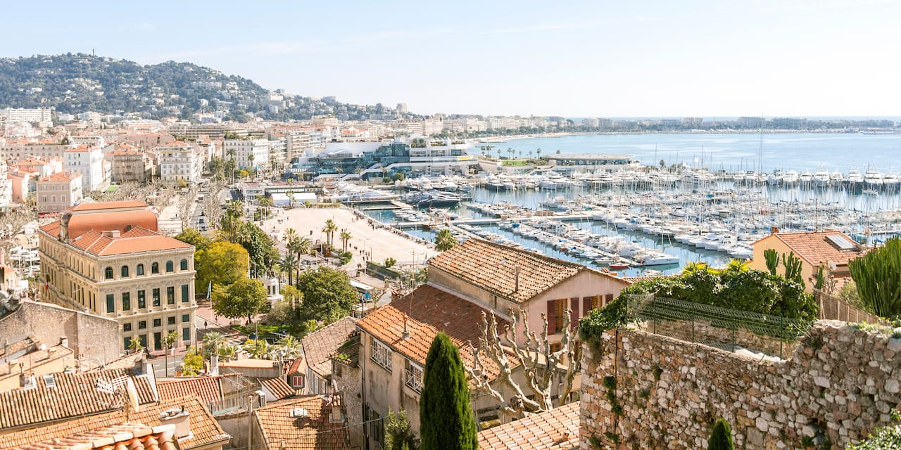 Boats docked in the Cannes Harbor with multi-storied, tile roof buildings hugging the shore