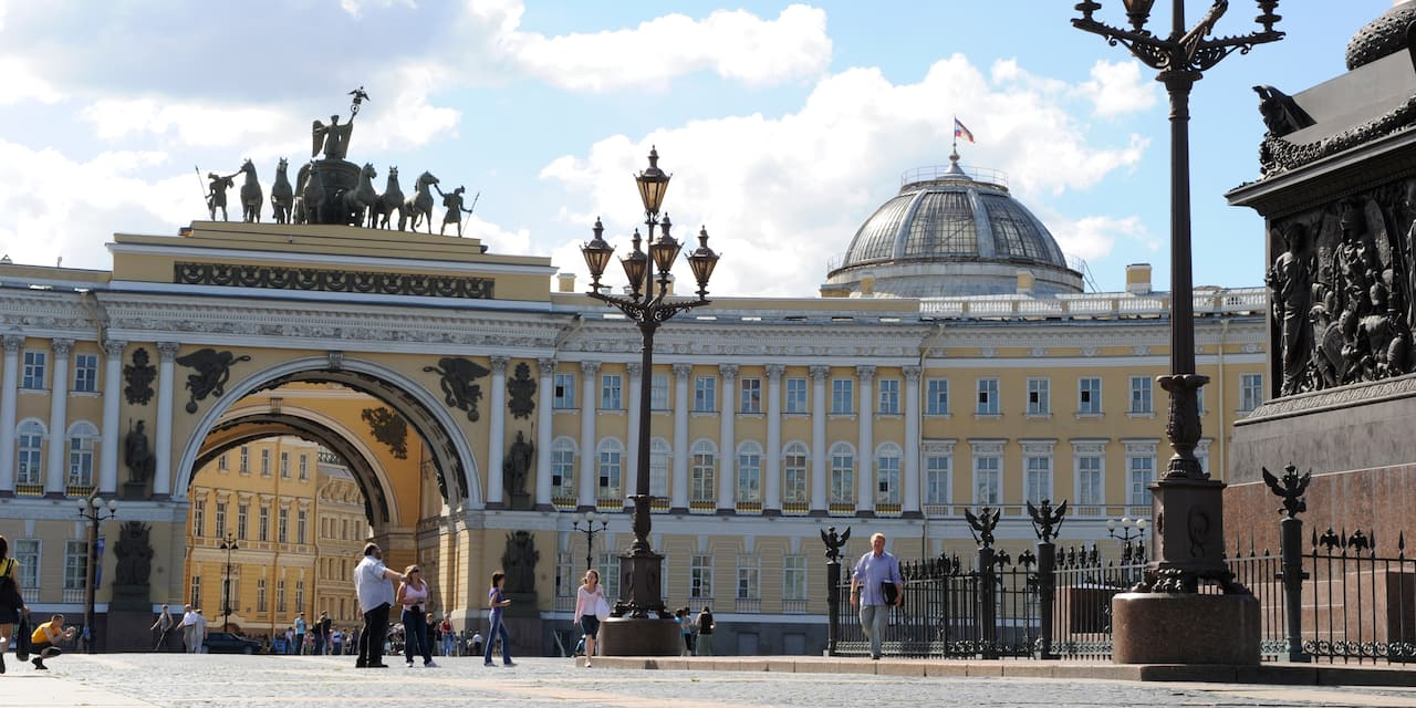 People walk in a courtyard near an archway with a statue on top and a domed building at the Hermitage Museum in St. Petersburg, Russia